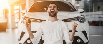 Excited guy in front of new car.